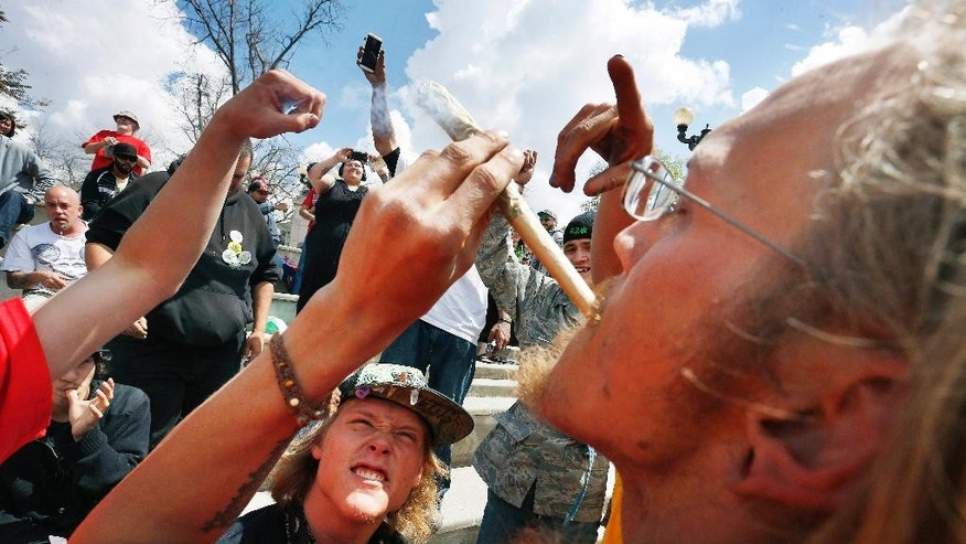 Partygoers listen to music and smoke marijuana on one of several days of the annual 4/20 marijuana festival, in Denver's downtown Civic Center Park, Saturday April 18, 2015. The annual event is the second 4/20 marijuana celebration since retail marijuana stores began selling in January 2014. (AP Photo/Brennan Linsley)