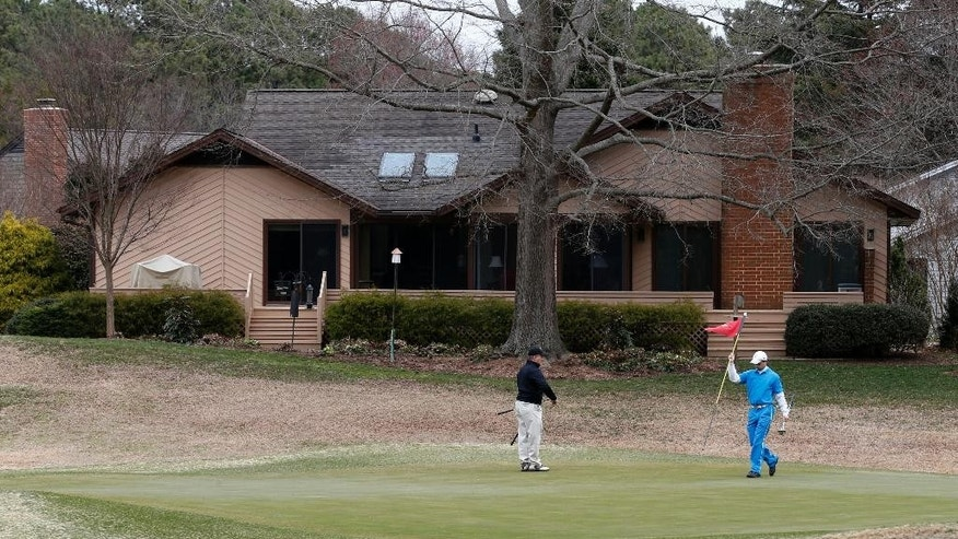 In this photo taken March 19, 2015, golfers enjoy the 14th hole in front of a luxury home in the Kingsmill resort in Williamsburg, Va. The last man to shoot an American president now spends most of the year in a house overlooking the 13th hole of a golf course in a gated community. He takes long walks along tree-lined paths, plays guitar and paints, grabs fast food at Wendy's. He drives around town in a silver Toyota Avalon, a car that wouldn't attract a second glance. Often, as if to avoid detection, he puts on a hat or visor before going out. These days, John Hinckley Jr. lives much of the year like any average Joe: shopping, eating out, watching movies at Regal Cinemas. (AP Photo/Steve Helber)