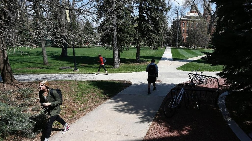 Students walk to and from classes on the campus quad of the University of Colorado, in Boulder, Colo., Monday April 20, 2015. The University of Colorado is open to the public on this 4/20 marijuana holiday for the first time in three years. The university has blocked public access in recent years in an effort to snuff mass smokeouts to mark the unofficial marijuana celebration. (AP Photo/Brennan Linsley)
