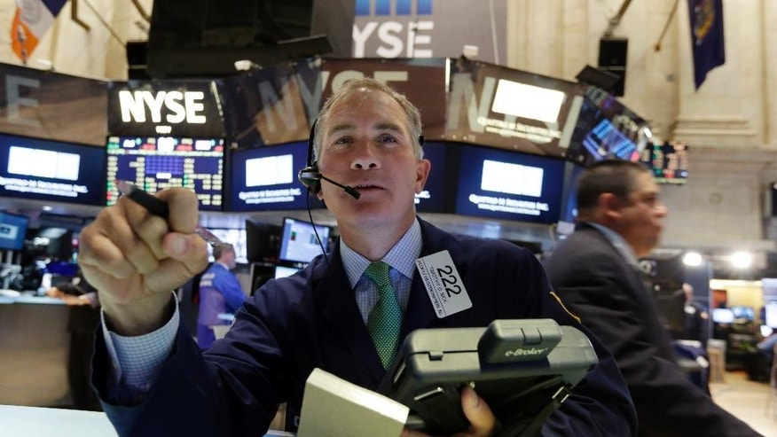 Trader Timothy Nick works on the floor of the New York Stock Exchange, Monday, April 20, 2015. U.S. stocks are opening higher as more big companies turn in healthy financial results for the first quarter of the year. (AP Photo/Richard Drew)