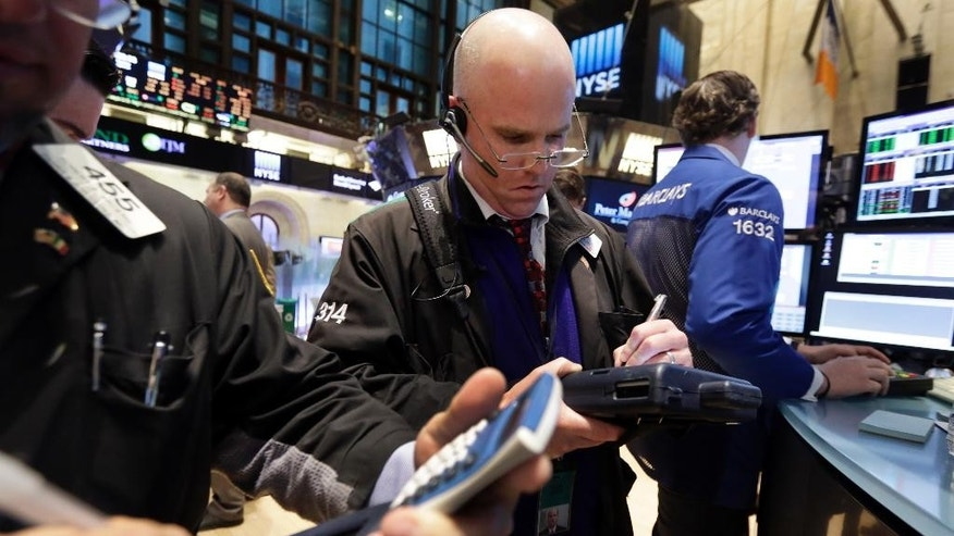 Trader Kevin Walsh, center, works, on the floor of the New York Stock Exchange Monday, April 20, 2015. U.S. stocks are opening higher as more big companies turn in healthy financial results for the first quarter of the year. (AP Photo/Richard Drew)