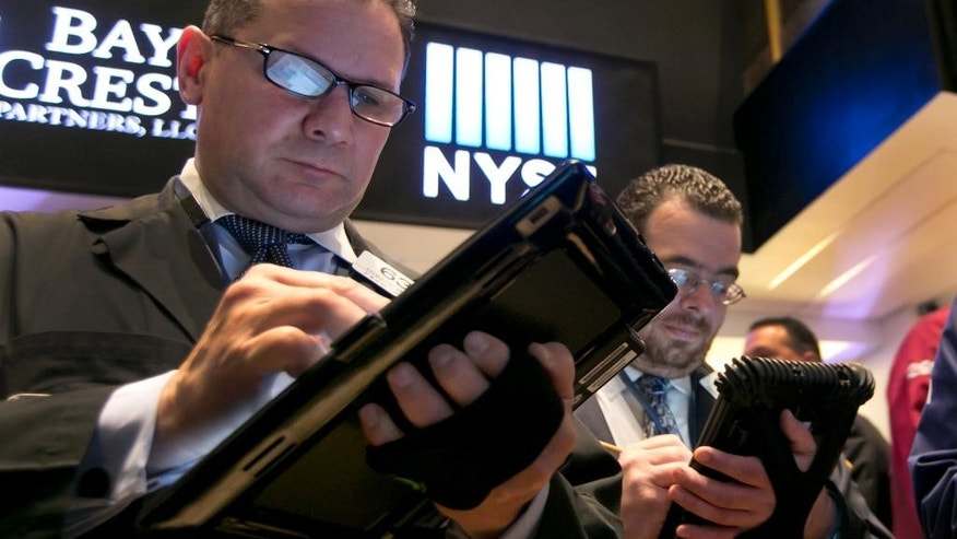 Trader Edward Curran, left, works on the floor of the New York Stock Exchange Monday, April 20, 2015. U.S. stocks are opening higher as more big companies turn in healthy financial results for the first quarter of the year. (AP Photo/Richard Drew)