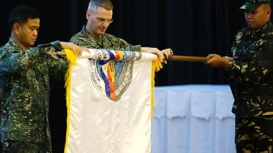 "Co-chairs of the joint U.S.-Philippines ""Balikatan 2015"" military exercise Philippine Navy Vice-Admiral Alexander Lopez, left, and U.S. Marine Brig. Gen. Christopher Mahoney, center, unfurl the Balikatan flag during the exercise's opening ceremony Monday, April 20, 2015 at Camp Aguinaldo at suburban Quezon city, northeast of Manila, Philippines. More than ten thousand troops from both countries' militaries are taking part in the annual military drill that focuses on regional security, terrorism, disaster preparedness and inter-operability. (AP Photo/Bullit Marquez)"