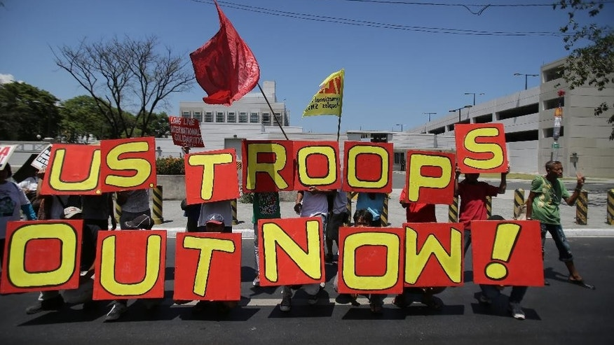 "Filipino activists hold slogans during a rally in front of the U.S. embassy in Manila, Philippines on Monday, April 20, 2015. The group is protesting against a joint U.S.-Philippines military exercise dubbed ""Balikatan 2015"" where troops from both countries take part in an annual drill that focuses on regional security, terrorism, disaster preparedness and inter-operability. (AP Photo/Aaron Favila)"