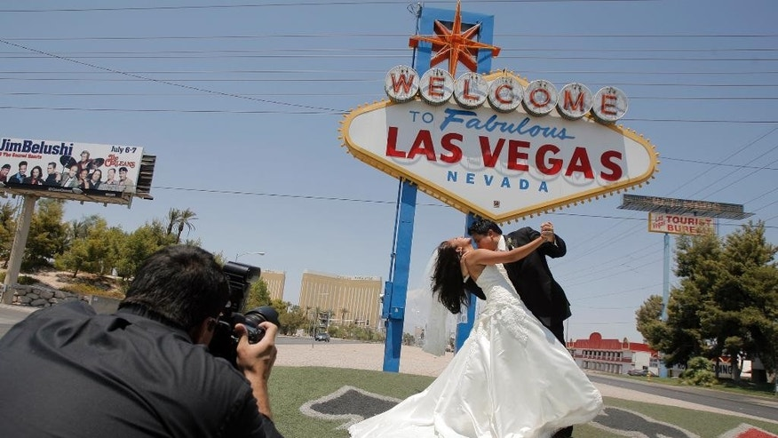 "FILE - In this July 7, 2007, file photo, Wedding photographer Sergio Lopez, left, take pictures of newly-weds Joseph Buangan and his wife Joyce, both of Torrance, Calif., with the ""Welcome to Fabulous Las Vegas"" neon sign in the background in Las Vegas. Betty Willis, the woman who designed the iconic neon sign that has welcomed countless visitors to Las Vegas since 1959 has died. She was 91. (AP Photo/Jae C. Hong, File)"