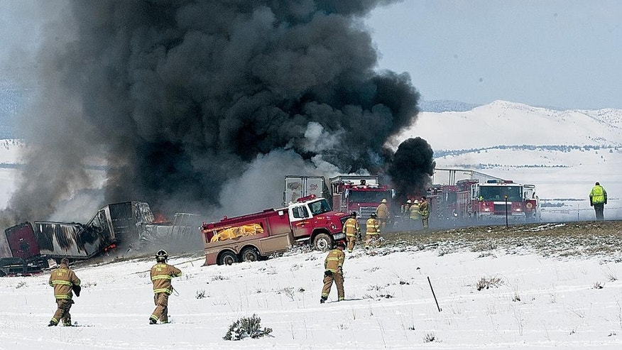 Smoke rises as emergency personnel respond to a a fiery chain-reaction crash on Interstate 80 near Laramie, Wyo., on Monday, April 20, 2015. Crews worked Tuesday to reopen Interstate 80 in southeastern Wyoming where a fiery chain-reaction crash the day before left one person dead and another in custody.  Wreckage from some 60 vehicles involved in the crash was still being removed Tuesday morning. In addition, engineers were assessing damage caused to the pavement by a fire that was started by the crash. (Peter Baumann/Laramie Daily Boomerang via AP)