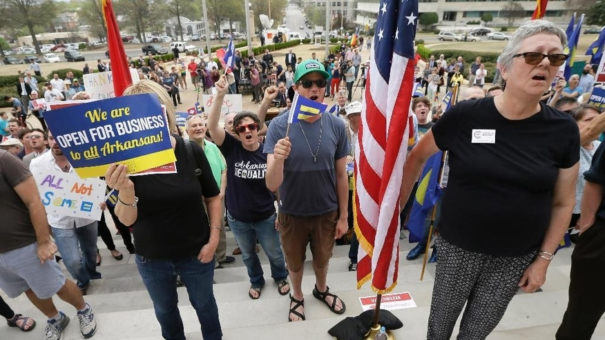 In this photo taken April 1, 2015, pro gay rights demonstrators gather at the Arkansas state Capitol in Little Rock, Ark. After the state became the epicenter of a fight over measures critics say are anti-gay, several Arkansas cities are trying to stem any potential fallout with efforts to push back on the new laws and expand anti-discrimination protections. (AP Photo/Danny Johnston)