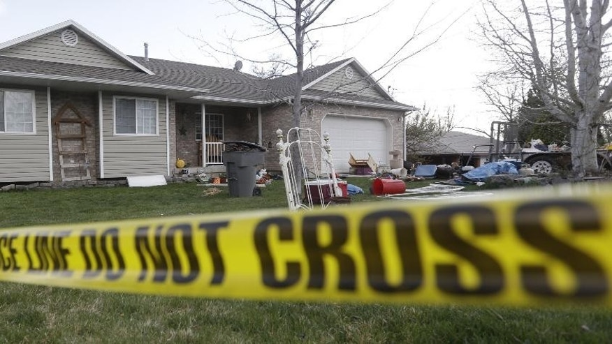 FILE- In this April 13, 2014, file photo Pleasant Grove Police police tape in front of the scene where seven infant bodies were discovered at the former home of Megan Huntsman in Pleasant Grove, Utah. Huntsman, who pleaded guilty to killing six of her newborn babies and hiding their bodies in her garage, was sentenced to up to life in prison Monday, April 20, 2015, in a case that drew national attention and sent shockwaves through the quiet community. (AP Photo/Rick Bowmer, File)