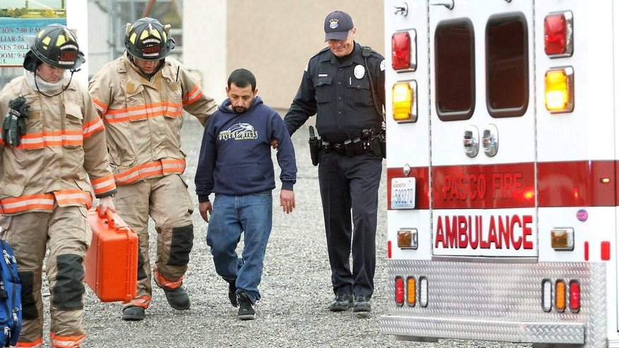 In this Jan. 22, 2015 photo, Pasco firefighters and Dean Perry, right, a Pasco police officer, help Antonio Zambrano-Montes, second from right, to an ambulance following a house fire in Pasco, Wash. On Feb. 10, 2015, Zambrano-Montes was fatally shot by police after he ran from them after throwing rocks at cars at an intersection in Pasco. Reports about Zambrano-Montes' interactions with police, obtained by The Associated Press through a public records request, provide new details about his behavior and the extent to which the Pasco Police Dept. was aware of his issues. (Bob Brawdy/Tri-City Herald via AP)