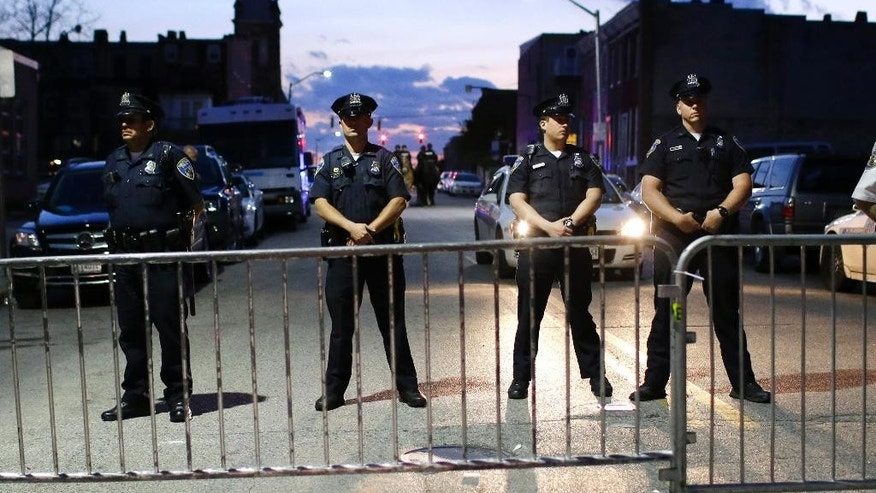 Members of the Baltimore Police Department stand behind barriers outside of the Western District police station during a march for Freddie Gray, Tuesday, April 21, 2015, in Baltimore. Gray died from spinal injuries about a week after he was arrested and transported in a police van. (AP Photo/Patrick Semansky)