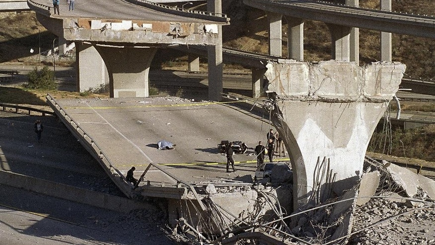 FILE - In this Jan. 17, 1994 file photo, the covered body of Los Angeles Police Officer Clarence Wayne Dean, 46, lies near his motorcycle which plunged off the State Highway 14 overpass that collapsed onto Interstate 5, after a magnitude-6.7 Northridge earthquake. The U.S. Geological Survey said more than 143 million people in the continental U.S. live in an earthquake zone and are exposed to potentially damaging ground shaking. (AP Photo/Doug Pizac, File)
