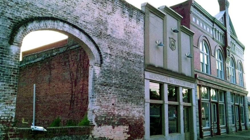 "This Oct. 1, 2013 photo shows the archways and brick wall of an old building in Grantville, Ga., that is used to film a scene in the AMC TV drama ""The Walking Dead."" Nine buildings in downtown Grantville where hit television drama The Walking Dead was filmed are up for sale. Grantville's former mayor says the structures,  virtually the entire downtown, are on the eBay online auction block until Friday, April 24, 2015, in hopes of finding a buyer who can breathe new life into the town on the southern fringe of metro Atlanta. (AP Photo/Jeff Martin)"