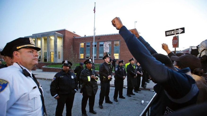 Protestors stand outside the Edward A. Garmatz United States District Courthouse during a march for Freddie Gray, Thursday, April 23, 2015, in Baltimore. Gray died from spinal trauma a week after being arrested by a group of officers, hoisted into police van and driven to a Baltimore station.  (AP Photo/Patrick Semansky)