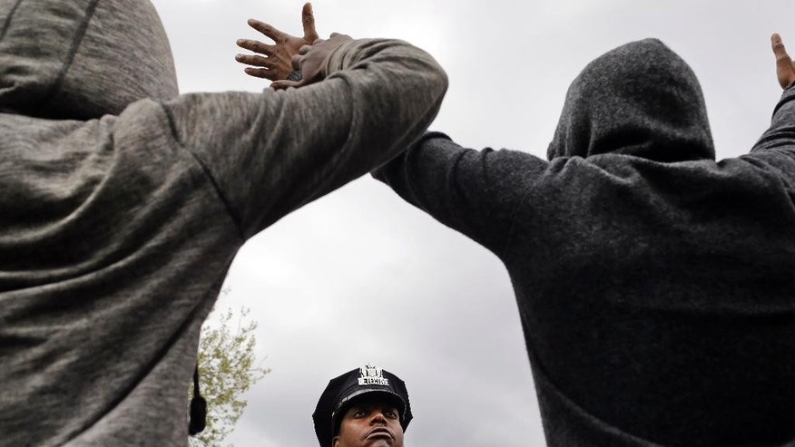 A member of the Baltimore Police Department stands guard outside of the department's Western District police station as men hold their hands up in protest during a march for Freddie Gray, Wednesday, April 22, 2015, in Baltimore. Gray died from spinal injuries about a week after he was arrested and transported in a police van. (AP Photo/Patrick Semansky)