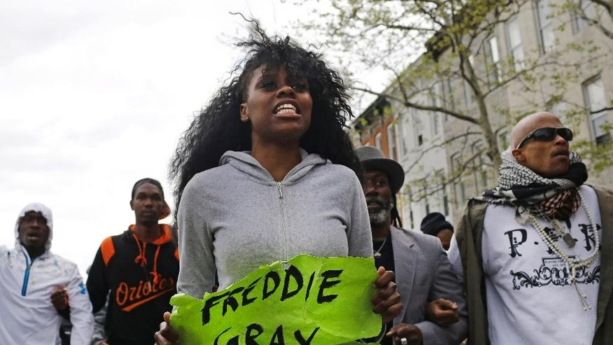 Protestors march for Freddie Gray toward the Baltimore Police Department's Western District police station, Wednesday, April 22, 2015, in Baltimore. Gray died from spinal injuries about a week after he was arrested and transported in a police van. (AP Photo/Patrick Semansky)