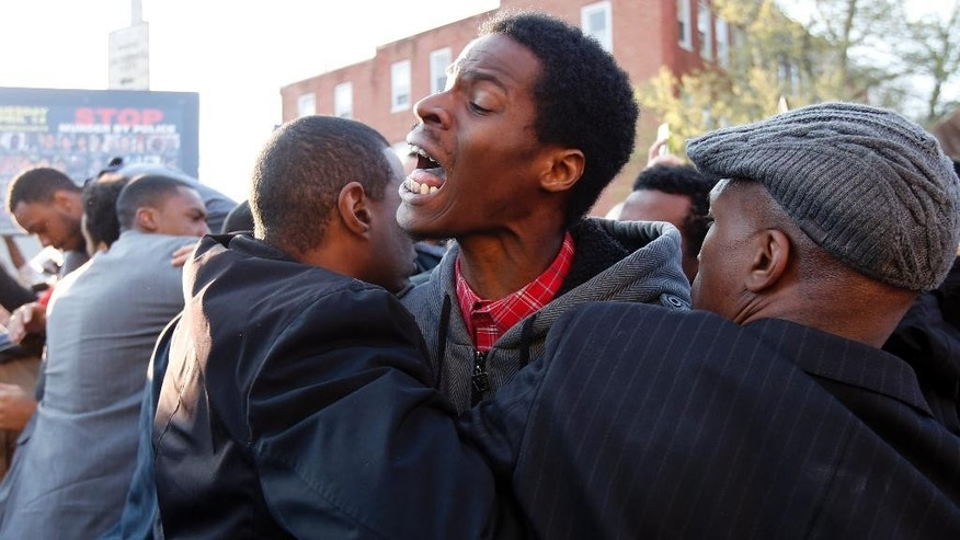 A man is restrained by fellow marchers as he yells at the Baltimore police guarding the department's Western district police station during a march for Freddie Gray, Wednesday, April 22, 2015, in Baltimore. Gray died from spinal injuries about a week after he was arrested and transported in a police van. (AP Photo/Alex Brandon)