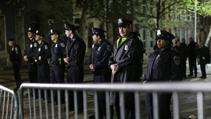 Members of the Baltimore Police Department stand guard behind a barrier outside the department's Western District police station during a protest for Freddie Gray, Wednesday, April 22, 2015, in Baltimore. Gray died from spinal injuries about a week after he was arrested and transported in a police van. (AP Photo/Patrick Semansky)