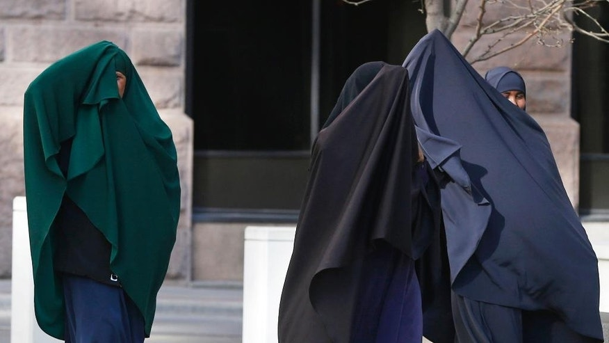 Members of Minnesota's Somali community cover their faces as they arrive Thursday, April 23, 2015, for a  detention hearing in federal court in St. Paul, Minn. for four of the six Minnesotans who are accused of plotting to travel to Syria to join the Islamic State group. Prosecutors have said they plan to ask a judge to keep the men in custody pending trial, saying they are a flight risk. (AP Photo/Jim Mone)