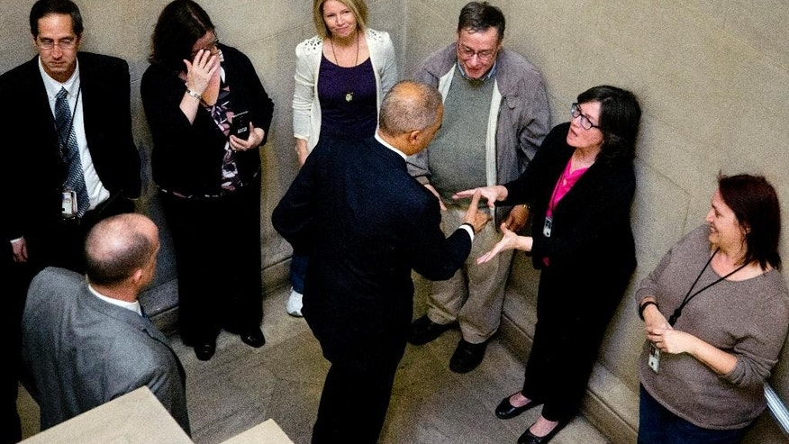 Justice Department employees line up to bid goodbye to Attorney General Eric Holder as he leaves the Justice Department building in Washington, Friday, April 24, 2015. Holder was bidding farewell to the Justice Department on Friday after six years as the nation's top law enforcement official. Holder -was addressing employees at an afternoon ceremony one day after his chosen successor, Loretta Lynch, was confirmed by the Senate -following a months-long delay.  (AP Photo/Manuel Balce Ceneta)