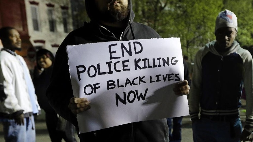 A man holds a sign during a protest for Freddie Gray outside the Baltimore Police Department's Western District police station, Thursday, April 23, 2015, in Baltimore. Gray died from spinal injuries about a week after he was arrested and transported in a police van. (AP Photo/Patrick Semansky)