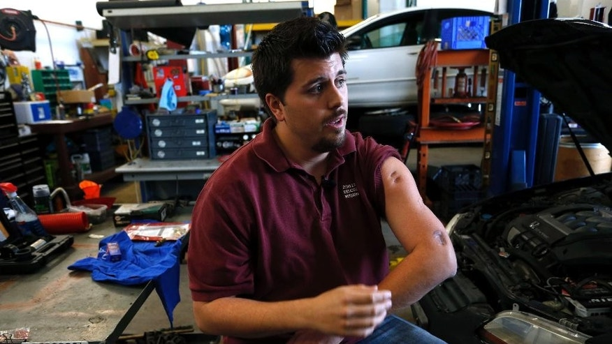 In this April 21, 2015 photo, Aurora movie theater shooting survivor Pierce O'Farrill shows some of his now-healed bullet wounds while giving an interview inside the repair shop at the Denver Rescue Mission's vehicle donation program, which he runs, in Denver. Nearly three years may have passed since James Holmes, wearing body armor, opened fire in a deadly attack at a packed Colorado movie theater, but many survivors - and relatives of the dead - are still trying to make sense of the shooting. (AP Photo/Brennan Linsley)