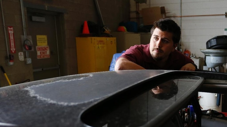 In this April 21, 2015 photo, Aurora movie theater shooting survivor Pierce O'Farrill looks over a donated car inside the repair shop at the Denver Rescue Mission's vehicle donation program, which he runs, in Denver. O'Farrill, who was wounded in the July 2012 shooting, said forgiveness and faith long ago gave him what others hope will come out of the upcoming trial: closure. (AP Photo/Brennan Linsley)