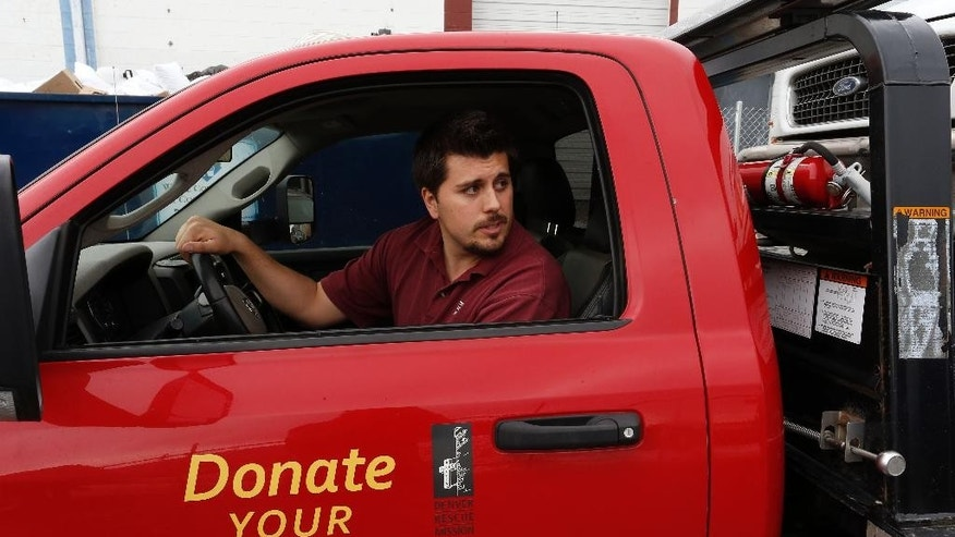 "In this April 21, 2015 photo, Aurora movie theater shooting spree survivor Pierce O'Farrill reverses a flatbed tow truck at the Denver Rescue Mission's vehicle donation program, which he runs, in Denver. O'Farrill, who was wounded in the July 2012 shooting, says that the morning after the shooting, he flipped through TV channels from a hospital bed. When he saw a photo of the now-defendant James Holmes, he remembered moments in his own teens and early 20s when he had been depressed and suicidal. ""I felt forgiveness,"" he said. (AP Photo/Brennan Linsley)"