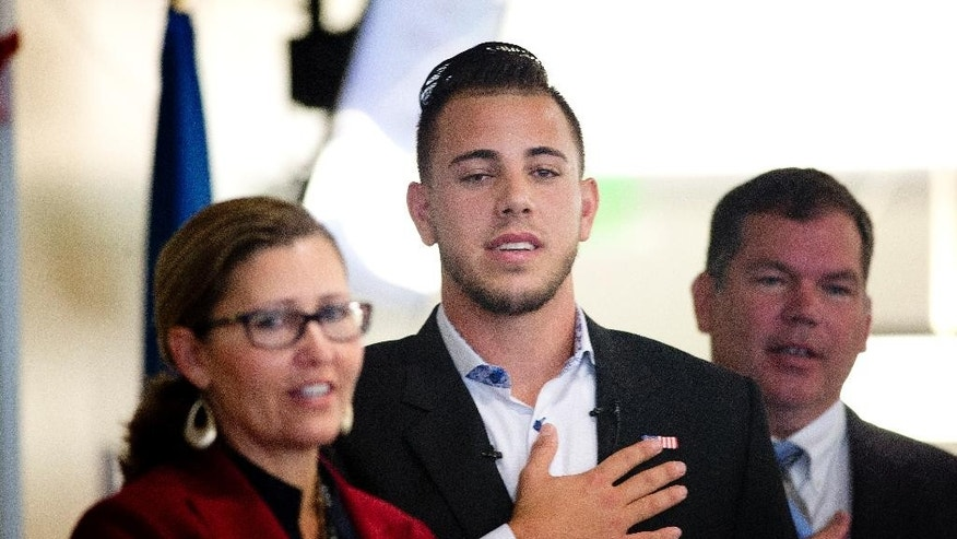 "Miami Marlins pitcher Jose Fernandez, center, and immigration officials recite the ""Pledge of Allegiance"" as Fernandez becomes a U.S. citizen during a naturalization ceremony Friday, April 24, 2015, in Miami. (AP Photo/J Pat Carter)"