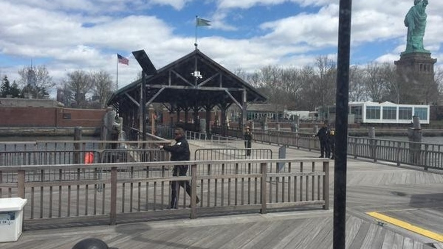 This photo, taken by tourist Rick Borgmeyer, of St. Louis, Mo., shows New  York City Police officers inspecting the perimeter of Liberty Island Friday after reports of a suspicious package.