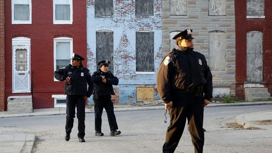 Members of the Baltimore Police Department walk near the intersection where Freddie Gray was arrested, Friday, April 24, 2015, in Baltimore. Gray died from spinal injuries about a week after he was arrested and transported in a police van. (AP Photo/Patrick Semansky)
