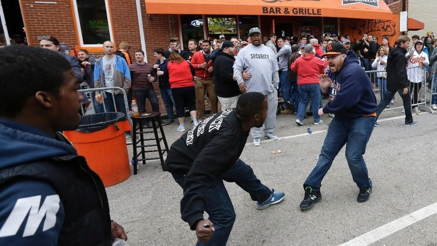 Protestors confront a patron outside of a bar across the street from Oriole Park at Camden Yards after a rally for Freddie Gray, Saturday, April 25, 2015, in Baltimore. Gray died from spinal injuries about a week after he was arrested and transported in a police van. (AP Photo/Patrick Semansky)