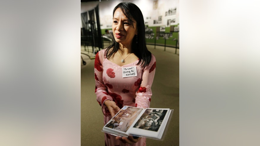 Kim Lan Duong, of Dallas, Texas, holds a photo album with photographs from a Vietnamese orphanage at three-years-old and the orphanage now, during ceremonies commemorating the 40th anniversary of Operation Babylift from Vietnam Friday, April 24, 2015, in Holmdel, N.J. Kim Lan Duong was a three-year-old when she was airlifted from Vietnam in Operation Babylift. (AP Photo/Mel Evans)