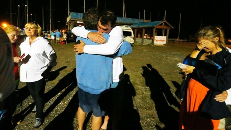 April 25, 2015: Well-wishers congratulate regatta participant Robert Luiten of Mobile, Ala., in blue shirt, on word that his son, Leonard Luiten, was found several hours after their boat capsized in a storm.