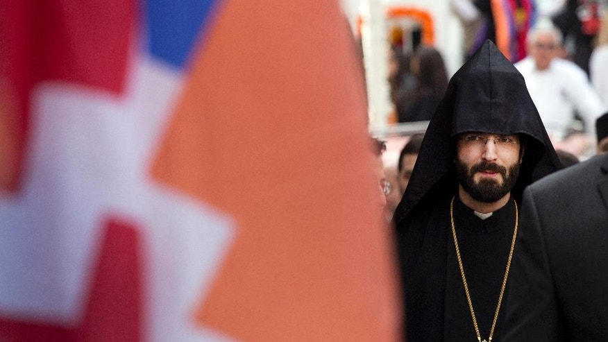 A priest with the Armenian Church of America marches in midtown Manhattan in New York to mark the centennial of the killings of as many 1.5 million Armenians under the Ottoman Empire _ today's Turkey _ on Sunday, April 26, 2015. Pro-Armenian activists are demanding that the U.S. government acknowledge the deaths during World War I as genocide. (AP Photo/Mark Lennihan)