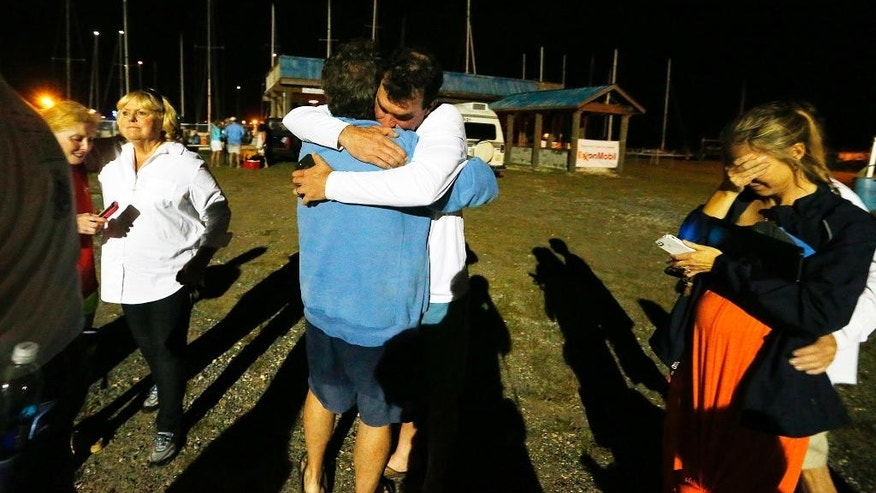 Well-wishers congratulate regatta participant Robert Luiten of Mobile, Ala., in blue shirt, on word that his son, Leonard Luiten, was found several hours after their boat capsized in a storm Saturday, April 25, 2015, in Dauphin Island, Ala. The Coast Guard says five people are missing after several sailboats participating in a regatta capsized during a storm in Mobile Bay Saturday. (AP Photo/Mike Kittrell, AL.com)