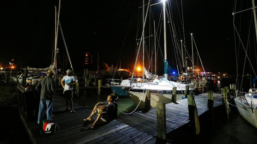 Dauphin Island Regatta sailors gather near their docked sailboats Saturday, April 25, 2015, in Dauphin Island, Ala. Coast Guard officials said they responded to a report of multiple capsized vessels around 4:30 p.m. Five people are missing after several sailboats participating in a regatta capsized during a storm in Mobile Bay Saturday according to the Coast Guard. (AP Photo/Mike Kittrell, AL.com)