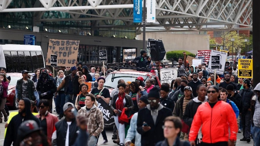 Marchers pass in front of the Baltimore Convention Center during a march to City Hall for Freddie Gray, Saturday, April 25, 2015 in Baltimore. Gray died from spinal injuries about a week after he was arrested and transported in a police van. (AP Photo/Alex Brandon)