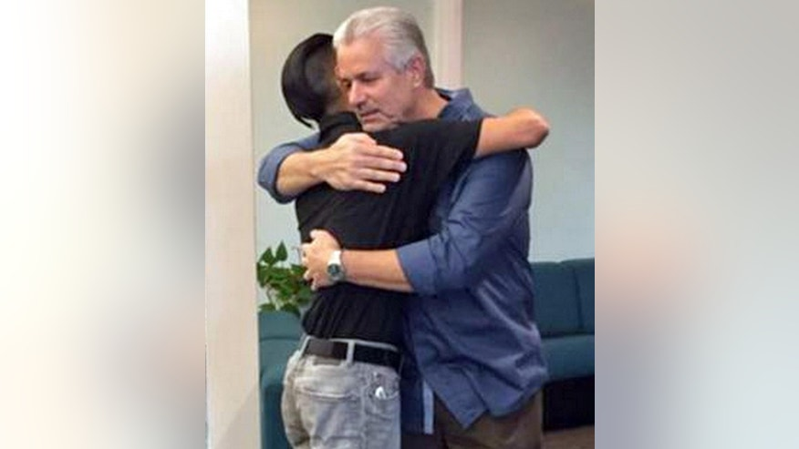 April 24, 2015: Retired Santa Ana, Calif., police officer Michael Buelna, right, embraces Robin Barton, now 25, as they are reunited in Santa Ana for the first time since Buelna found Barton as a newborn abandoned in a garbage dumpster in.
