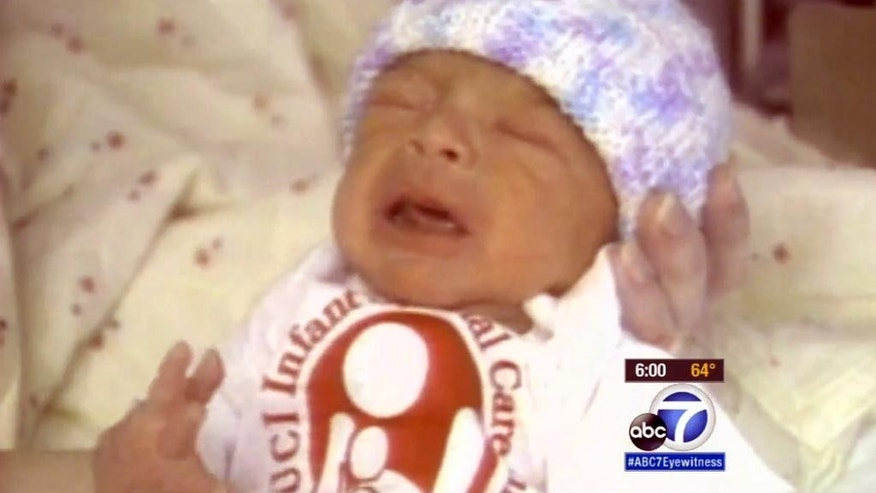 This November, 1989 still frame from video provided by KABC-TV shows Robin Barton, now 25, after his rescue by retired Santa Ana, Calif., police officer Michael Buelna as a newborn abandoned in a garbage dumpster.