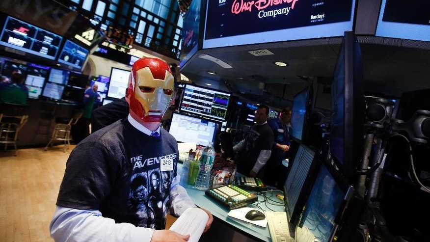 Trader John O'Hara wears an Ironman mask as he works on the floor of the New York Stock Exchange, Monday, April 27, 2015, in New York. Actors Jeremy Renner and Robert Downey Jr. rang the NYSE opening bell Monday with representatives from Marvel Entertainment. (AP Photo/Jason DeCrow)