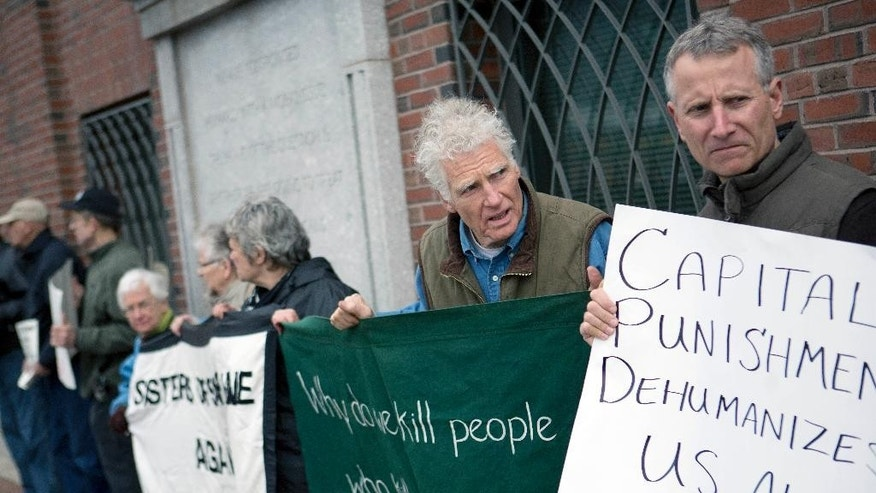 Death penalty protesters stand outside federal court, Monday, April 27, 2015, in Boston, during the penalty phase of the federal trial of Dzhokhar Tsarnaev, who was convicted of the Boston Marathon bombings that killed three and injured 260 people in April 2013. (AP Photo/Justin Saglio)