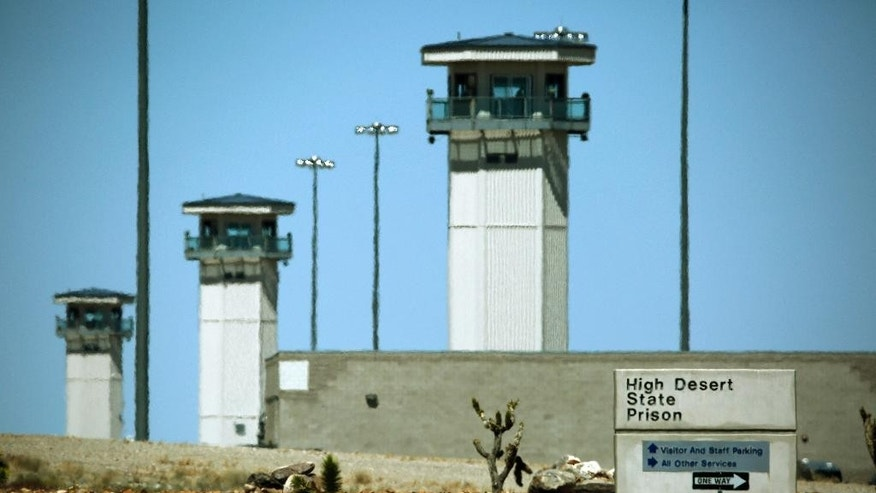 FILE - This April 15, 2015 file photo shows guard towers at High Desert State Prison in Indian Springs, Nev., one of Nevada's toughest prisons. Attorneys for two inmates involved in a deadly prison brawl are accusing prison guards of instigating the fight to set up a gladiator-style contest and then trying to cover it up by blaming the surviving prisoner. (AP Photo/John Locher, File)