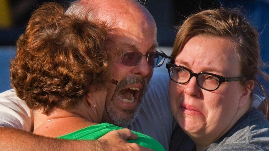 """FILE - In this July 20, 2012, file photo, Tom Sullivan, center, embraces family members outside Gateway High School where he had been searching for his son Alex Sullivan who was killed while attending """"The Dark Knight Rises,"""" movie where gunman James Holmes opened fire, in Aurora, Colo. Twelve people were killed and 70 others injured in the deadly shooting. (AP Photo/Barry Gutierrez, File)"""