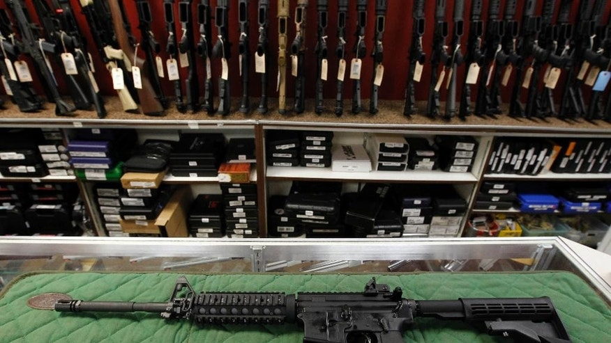 FILE - In this July 26, 2012, file photo, an AR-15 style rifle is displayed at the Firing-Line indoor range and gun shop in Aurora, Colo. Police say James Holmes donned body armor and was armed with an AR-15 rifle, a shotgun and two handguns during his attack on an Aurora movie theater. Holmes purchased 6,295 rounds of ammunition before the attack and had set up 30 homemade explosives set up in his apartment to go off at the time of the theater attack. They did not go off. (AP Photo/Alex Brandon, File)