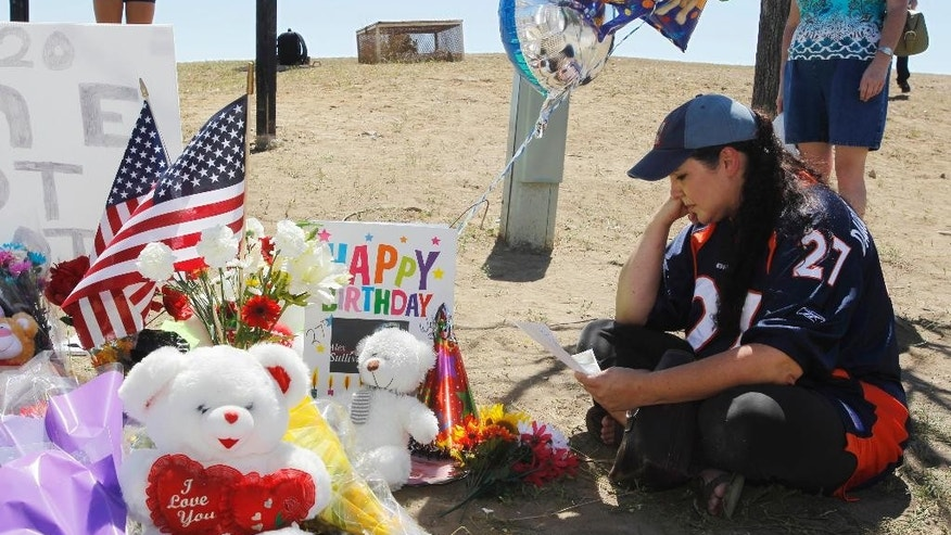 FILE - In this July 21, 2012, file photo, Shelly Fradkin, the mother of a friend of theater shooting victim Alex Sullivan, looks at a birthday card for Sullivan placed at a makeshift memorial across from the Century 16 theater, east of the Aurora Mall in Aurora, Colo. At least 10 lawsuits have been filed against the theater following the deadly shooting committed by James Holmes. (AP Photo/David Zalubowski, File)