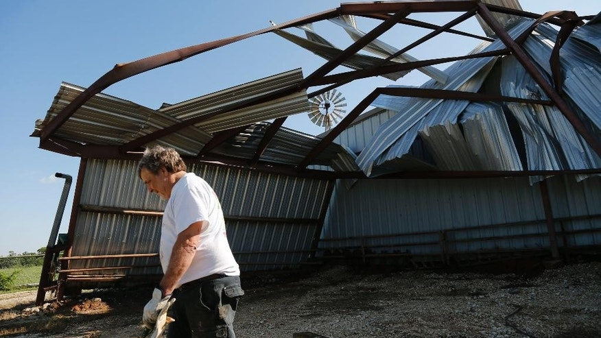 John Kuethe, owner of Green Acres Farm surveys the damage to his barn that was partially uprooted, damaging two tractors and much of the building, Monday, April 27, 2015, as residents east of Rio Vista, Texas clean up after a severe storm system swept across parts of Texas Sunday night. The storm brought numerous reports of tornadoes, damage to buildings, large hail and several inches of rain. There were no accounts of injuries. (Rodger Mallison/Fort Worth Star-Telegram via AP)