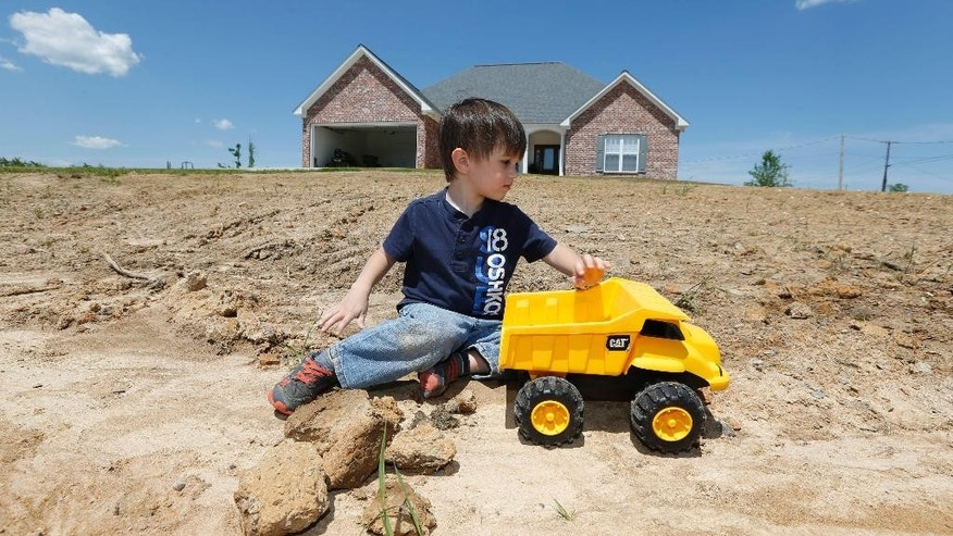 In this April 22, 2015 photograph, Ryan Blackwell, 3, plays on the yet-to-be developed front yard of his new house in Louisville, Miss., as the community marks the first anniversary of an April 28, 2014, tornado system that killed 10 people in Louisville and surrounding areas, and destroyed 391 buildings. Blackwell's family house, which was destroyed by the tornado, was a couple of houses down from this newly-constructed house. (AP Photo/Rogelio V. Solis)