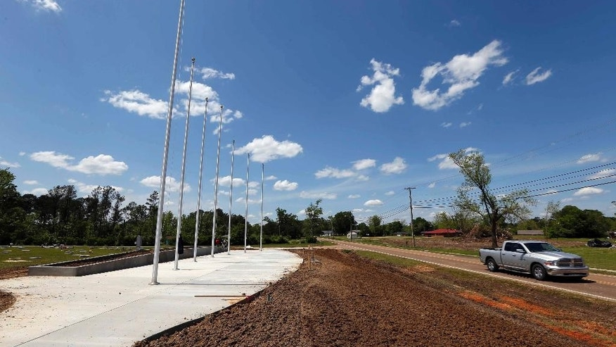 In this April 22, 2015 photograph, traffic rolls past the new addition at Memorial Park Cemetery in Louisville, Miss. The addition, which will feature flag displays, granite benches, trees and a flower garden, will be dedicated to the lives lost in the April 28, 2014, tornado. (AP Photo/Rogelio V. Solis)