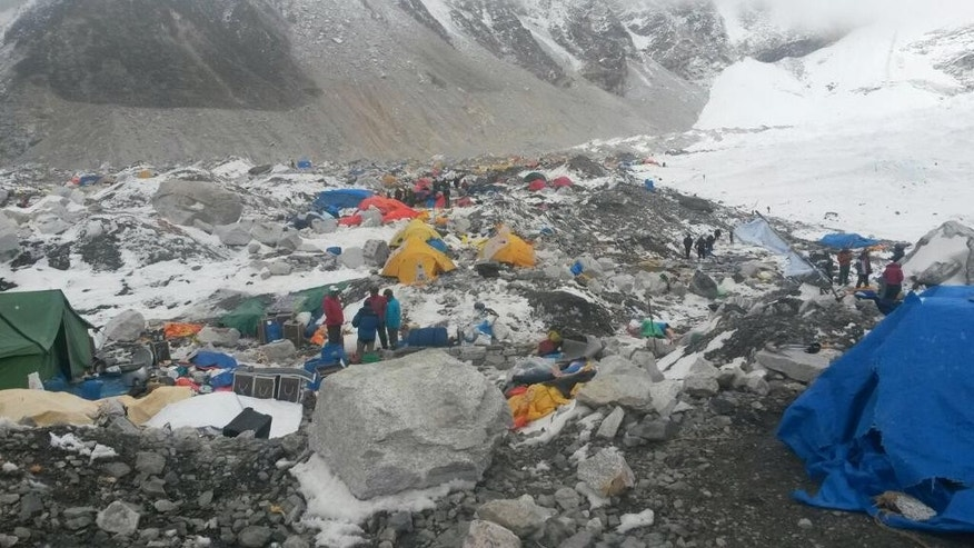 Mountain guides and climbers stand beside camping and climbing gear gathered together after an avalanche hit the area, at Everest Base Camp, Nepal, Tuesday, April 28, 2015. Saturday's quake unleashed an avalanche that buried part of the base camp packed with foreign climbers preparing for summit attempts. (AP Photo/Nima Namgyal Sherpa)