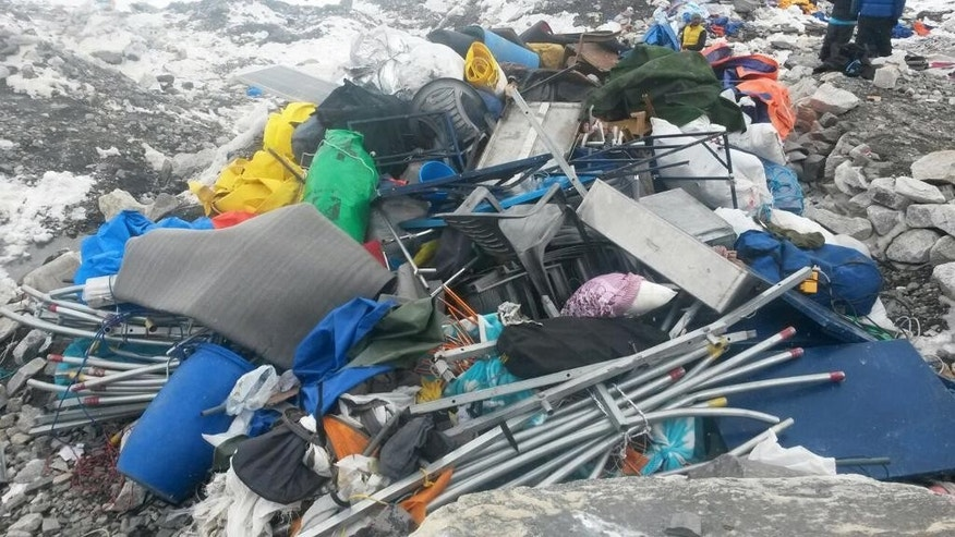 People gather camping and climbing equipment that was earlier strewn about after an avalanche hit the area on Saturday at Everest Base Camp, Nepal, Tuesday, April 28, 2015. An avalanche on Saturday, set off by the massive earthquake that struck Nepal, left more than a dozen people dead and dozens more injured. (AP Photo/Nima Namgyal Sherpa)